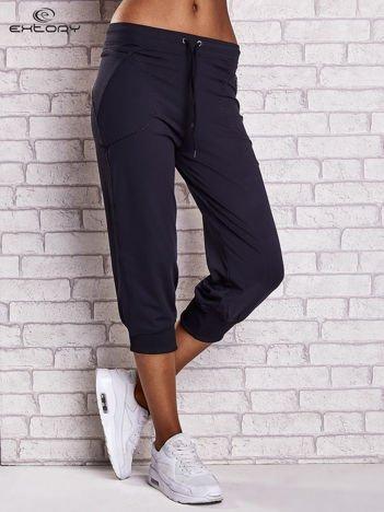 Granatowe spodnie capri z kieszonką i haftem PLUS SIZE