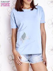 Jasnoniebieski t-shirt z ukośną kieszenią i dżetami