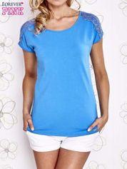 Niebieski t-shirt z koronkowym wykończeniem rękawów