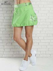 Zielona spódnica dresowa z nadrukami i troczkiem na dole