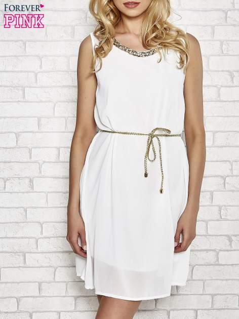 Biała sukienka ze złotym łańcuszkiem przy dekolcie