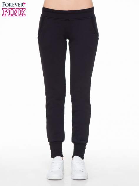 Czarne spodnie dresowe z guziczkami przy ściągaczu