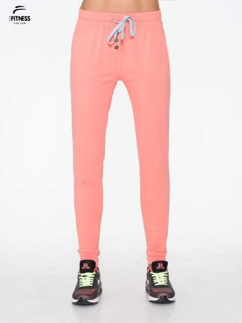 Jasnokoralowe spodnie dresowe typu baggy z guzikami