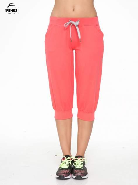 Koralowe spodnie sportowe typu capri wiązane w pasie