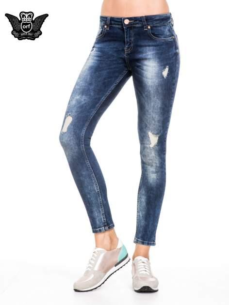 Niebieskie spodnie jeansowe rurki z lekkim dekatyzowaniem i przetarciami