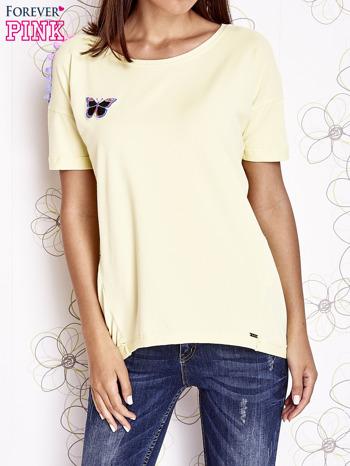 Żółty t-shirt z naszywką motyla i pomponami