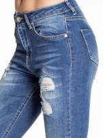 Ciemnoniebieskie spodnie skinny jeans z poszarpaną nogawką i dziurami