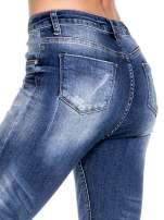Ciemnoniebieskie spodnie skinny jeans z przecieraną nogawką z przodu