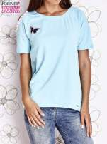 Turkusowy t-shirt z naszywką motyla i pomponikami