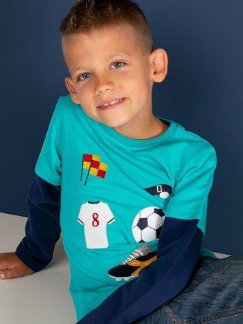 Bawełniana turkusowa bluzka dla chłopca ze sportowymi naszywkami