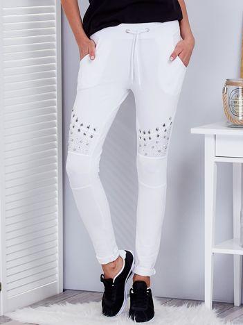 Białe spodnie dresowe z agrafkami i aplikacją na kolanach
