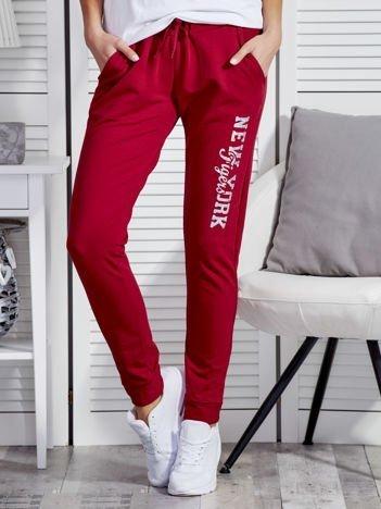 Bordowe spodnie dresowe z mieniącym się napisem