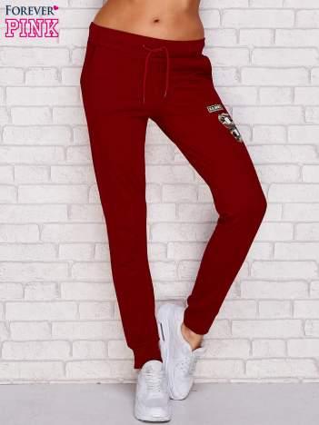 Bordowe spodnie dresowe z naszywkami