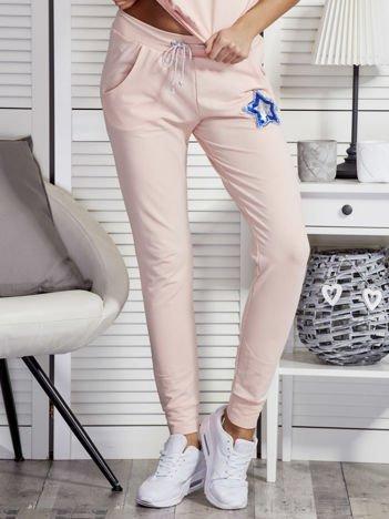 Brzoskwiniowe spodnie dresowe z cekinową gwiazdą