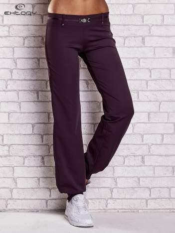 Ciemnofioletowe spodnie dresowe z ozdobnym paskiem
