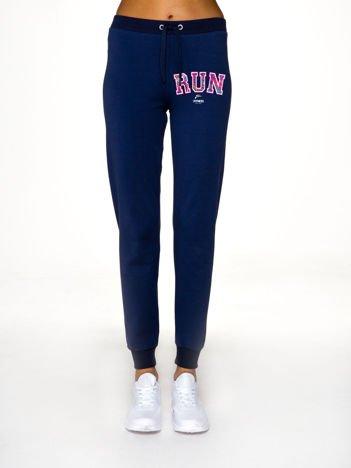 Ciemnoniebieskie spodnie dresowe ze sportowym nadrukiem