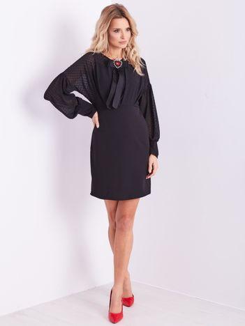Czarna sukienka z ozdobną broszką