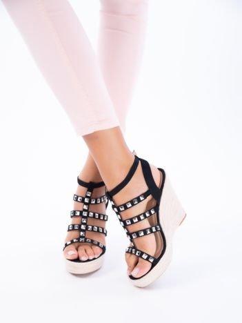 Czarne sandały na koturnach z ozdobnie plecionymi paskami oraz ćwiekami