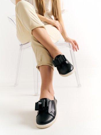Czarne skórzane półbuty na białej podeszwie z finezyjną kokardką z przodu buta