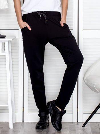 Czarne spodnie dresowe z błyszczącymi lampasami