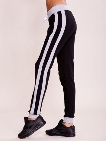 Czarne spodnie dresowe z kieszeniami i lampasami