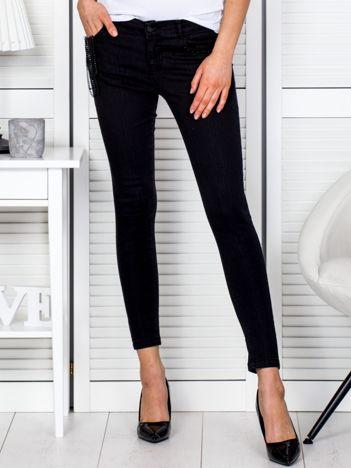 Czarne spodnie slim z łańcuszkami przy kieszeni