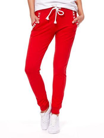 Czerwone spodnie dresowe z perełkami przy kieszeniach