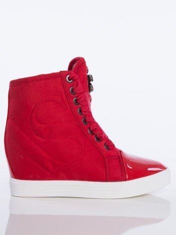 Czerwone zamszowe sneakersy z tłoczoną literką na boku cholewki, sznurowane ozdobną tasiemką z błyszczącymi kamieniami na przodzie