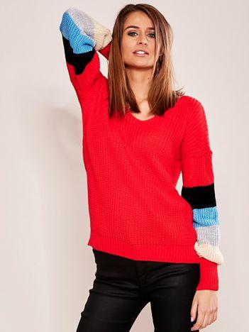 Czerwony sweter z rękawami w paski