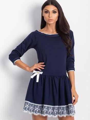 Granatowa sukienka z kokardką i szeroką falbaną