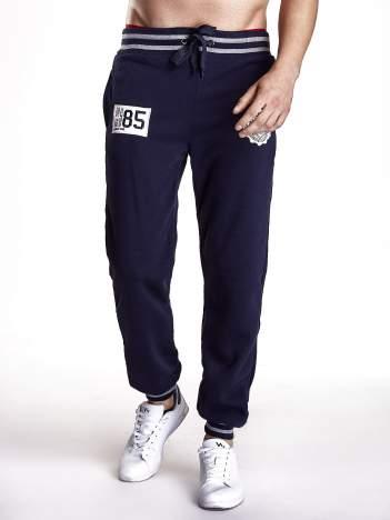 Granatowe dresowe spodnie z naszywkami i kieszeniami