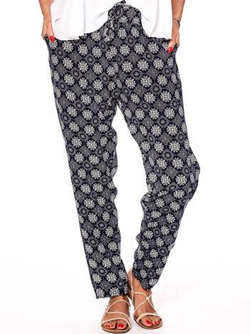 Granatowe materiałowe spodnie w ornamentowe wzory