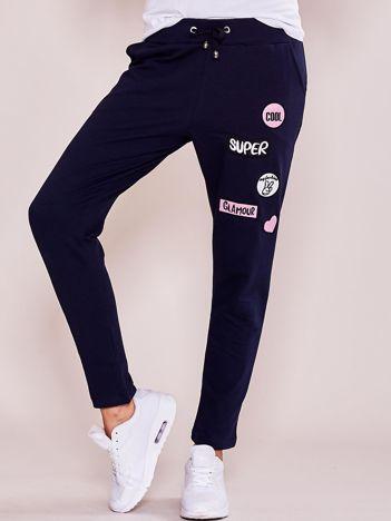 Granatowe spodnie dresowe z naszywkami