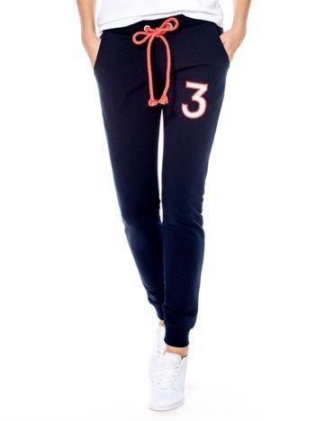 Granatowe spodnie dresowe z troczkami i błyszczącą cyfrą
