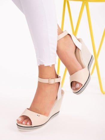 Jasnobeżowe sandały na wysokich koturnach, z biało-beżowymi paskami na na kostkach i kolorową podeszwą