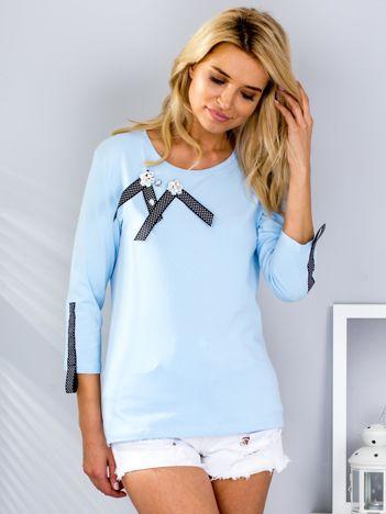 Jasnoniebieska bluzka z ozdobnymi przypinkami