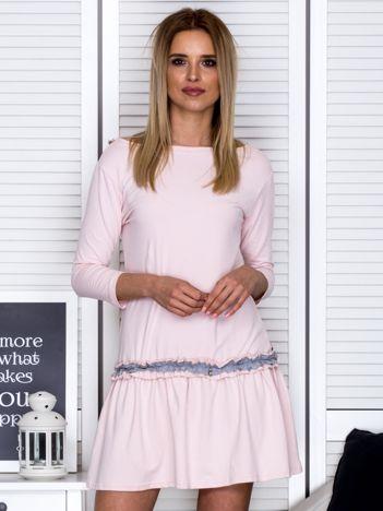 Jasnoróżowa sukienka z kontrastową falbanką