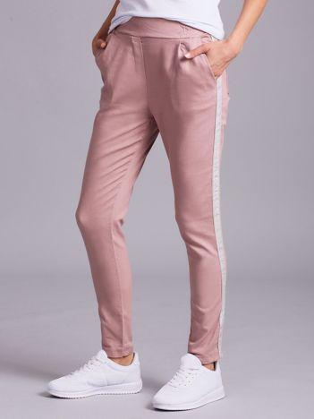 Jasnoróżowe damskie spodnie z lampasem