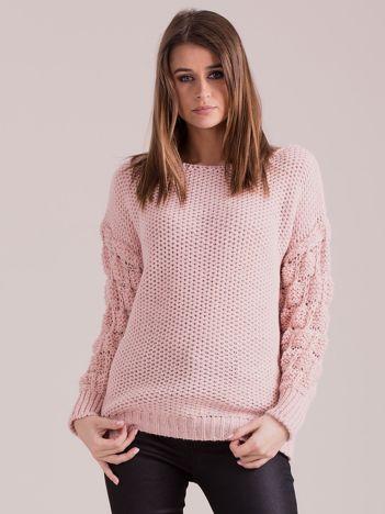 Jasnoróżowy sweter z plecionymi rękawami
