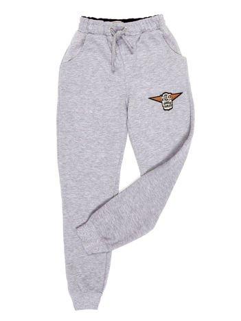 Jasnoszare spodnie dresowe dla chłopca z naszywką
