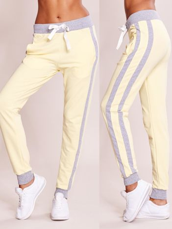 Jasnożółte spodnie dresowe z kieszeniami i lampasami
