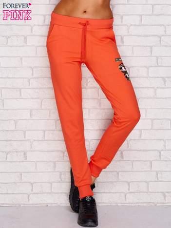 Koralowe spodnie dresowe z naszywkami