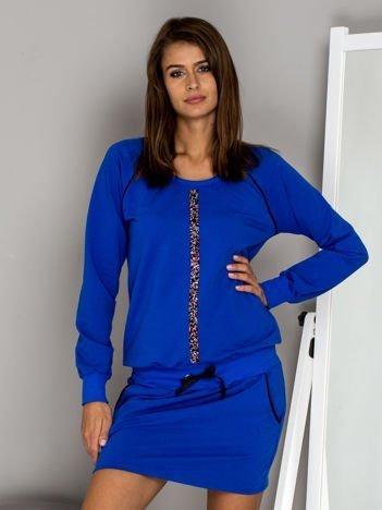 Niebieska sukienka z biżuteryjnym paskiem