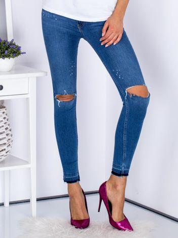 Niebieskie dopasowane jeansy z rozcięciami na kolanach