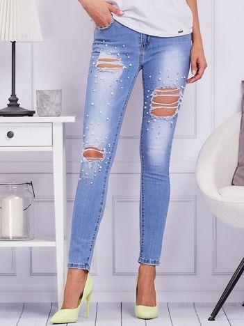 Niebieskie jeansy z dziurami i perełkami