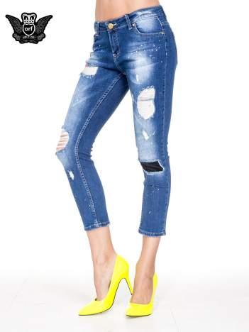 Niebieskie spodnie jeansowe długości 7/8 z łatami i przetarciami