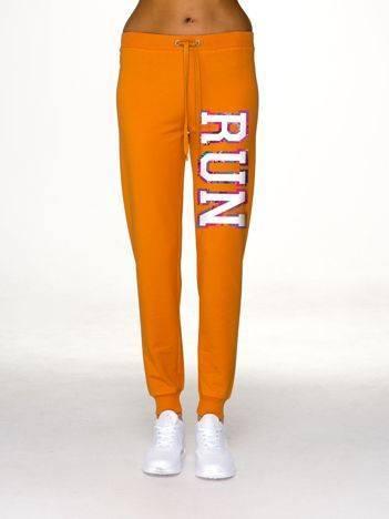 Pomarańczowe spodnie dresowe z napisem RUN na nogawce