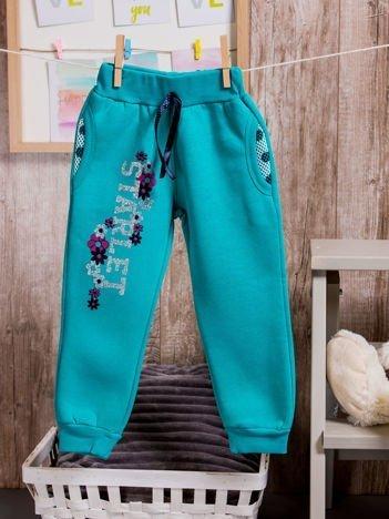 Spodnie dresowe dziewczęce z brokatowym nadrukiem turkusowe