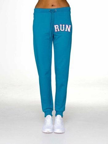 Spodnie dresowe z napisem RUN ciemnoturkusowe