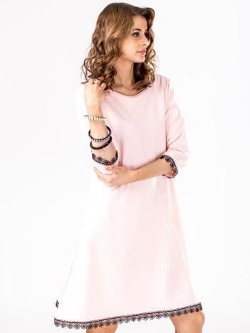 Sukienka jasnoróżowa z koronkowym wykończeniem